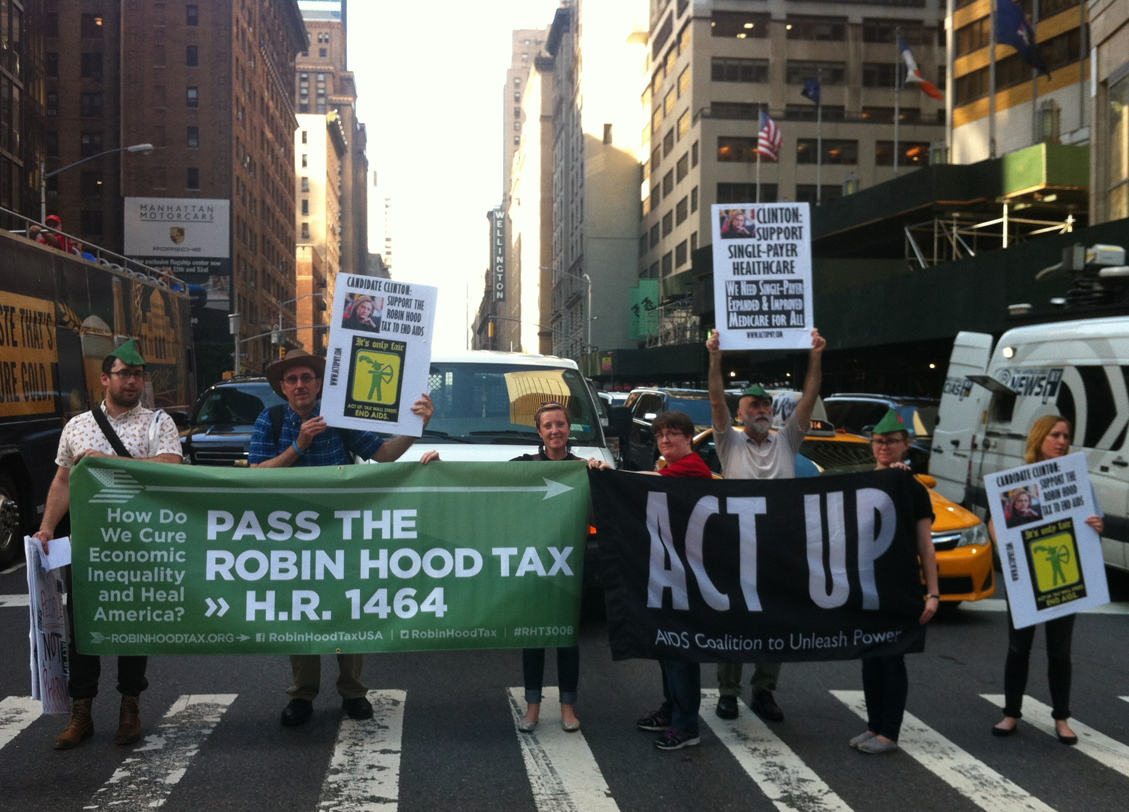Members of  ACT UP NY  group took to the street with protest signs and banners outside the  Sheraton Times Square , where Democratic Party presidential primary candidate  Hillary Rodham Clinton  was attending a fundraiser. Activists demanded a  tax  on Wall Street transactions to fund a  single-payer healthcare system  and affordable drug prices, which, when combined with other public health policy proposals, could end  AIDS .  Source :  Louis Flores/Progress Queens