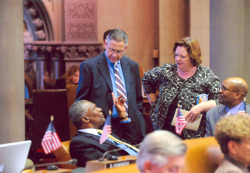 New York State Assemblymember  Keith Wright  (D-Harlem), seated at left, with left-to right : Former Speaker  Sheldon Silver  (D-Lower East Side), Assemblymember  Catherine Nolan  (D-Woodside), and former Assemblymember  Darryl Towns  (D-East New York) in an undated photograph. Since this photograph was taken, former Assemblymember Silver has been convicted of Federal corruption charges, and former Assemblymember Towns was appointed CEO of the  New York State Homes and Community Renewal . Source : New York State Assembly/Public Domain