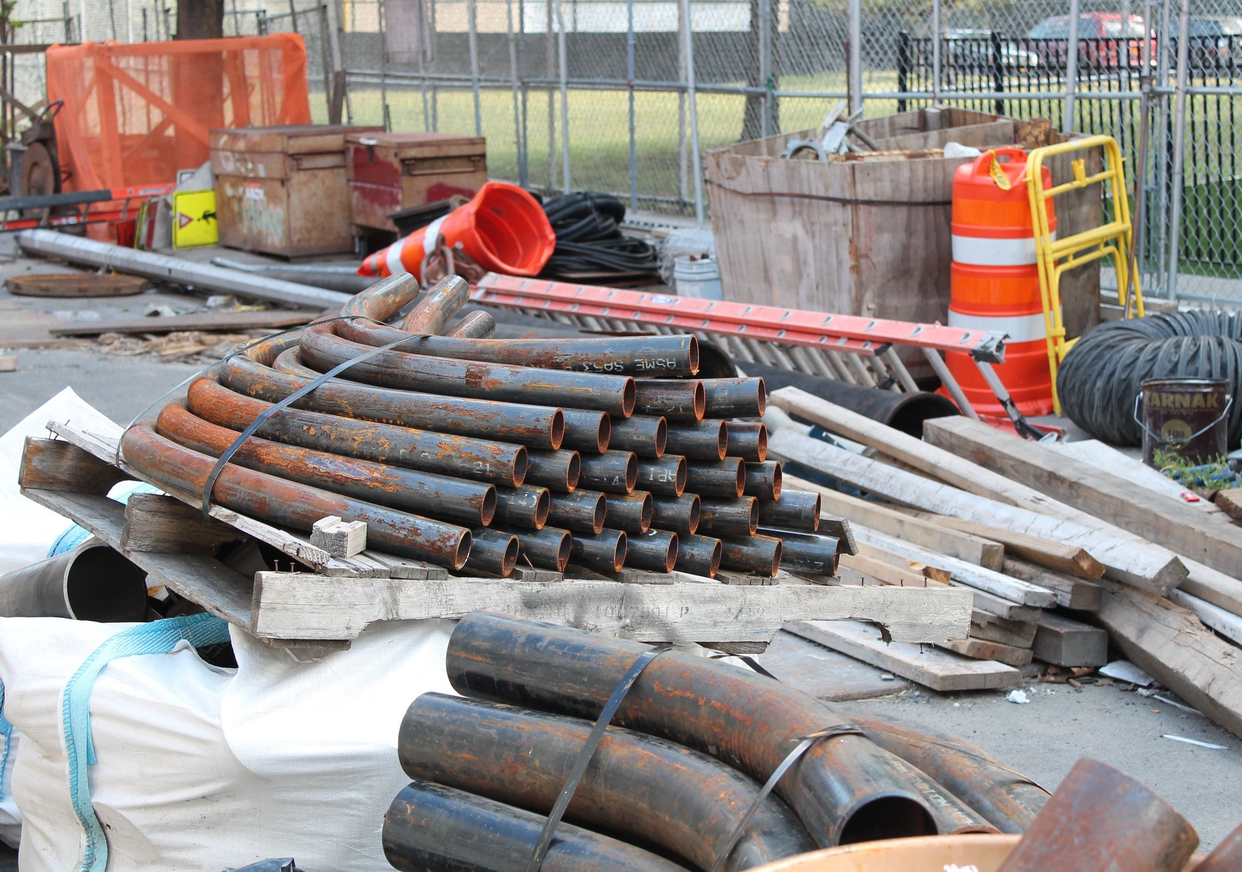 Inside an MTA staging area, construction materials were scattered inside a fenced-in zone alongside East 101st Street near the southeast corner of Second Avenue. Source : Louis Flores/Progress Queens