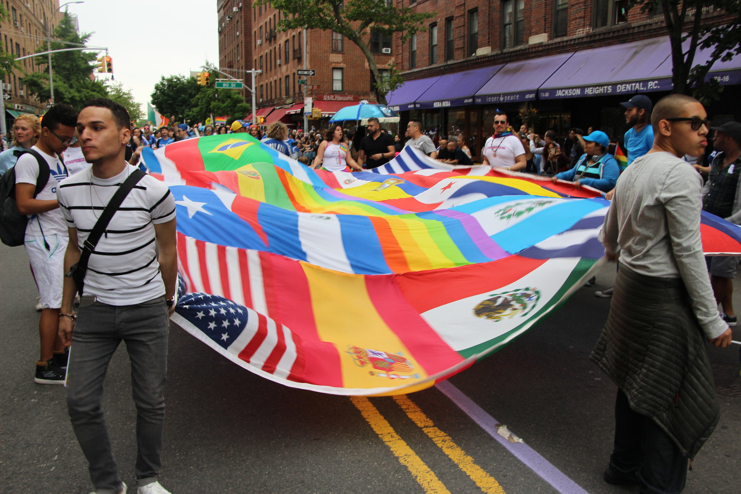 To signify LGBT diversity, some participants in the Queens Pride Parade carried a giant patchwork of various flags, including the  Rainbow Flag , the latter which was designed by the late  Gilbert Baker . The flags represented some of the backgrounds of the LGBT community in Queens. Source : Pauline Park/Used With Permission