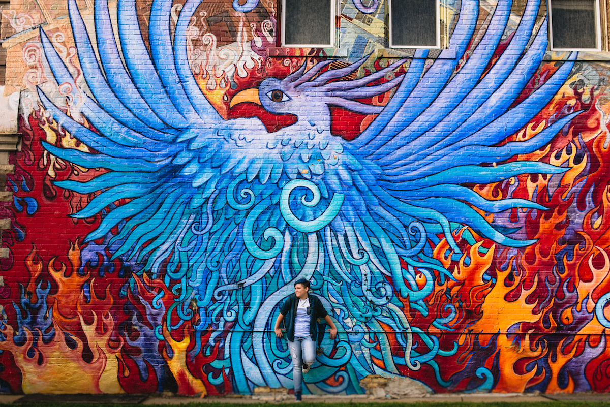 high school senior in front of a phoenix mural