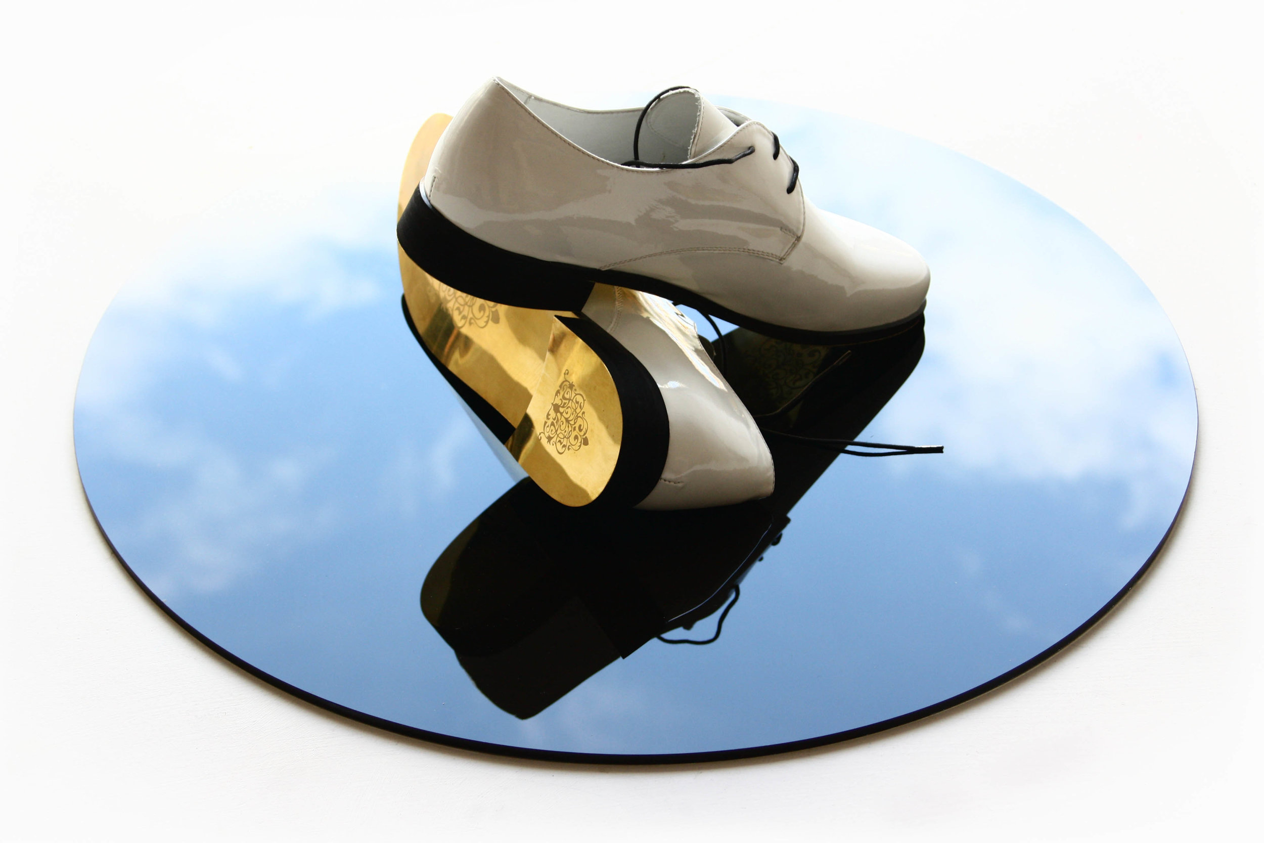 GOLDEN SHOES FOR GOLDEN ROUTES (2010) engraved bronze, leather, lacquer, black glass, 20 x 55 x 55 cm
