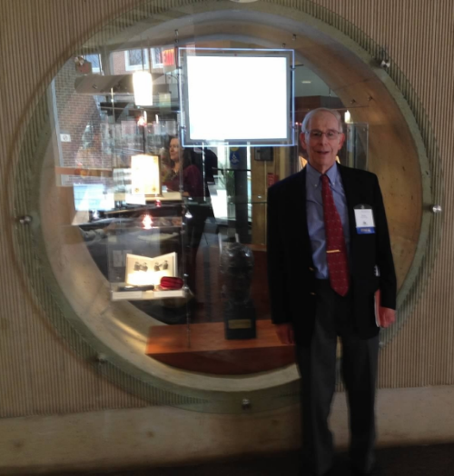 Dr. Albert in front of the exhibit, which surrounds a bust of Dr. Scheie, in the lobby of the Scheie Eye Institute.