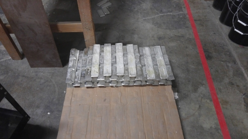 Stacks of pewter ingots waiting to become fantasy miniatures. Each one weighs about 15 pounds and can craft about 100 individual figures.
