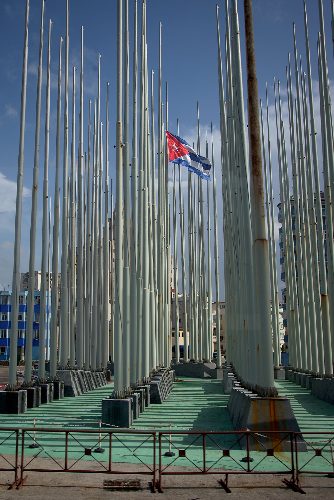 The Cuban flag flies alone in a plaza with dozens of empty flag poles