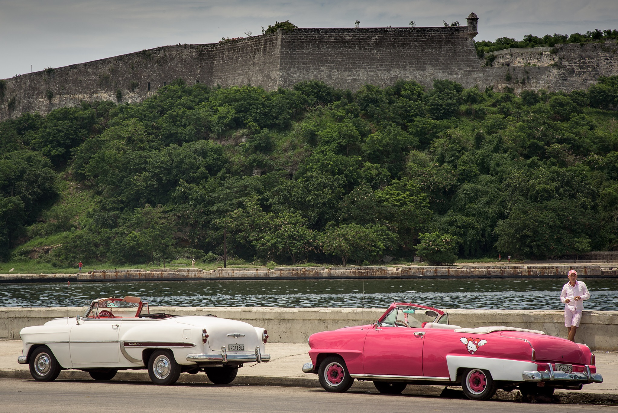 Some old cars along the Malecon in front of the Old Fortress.