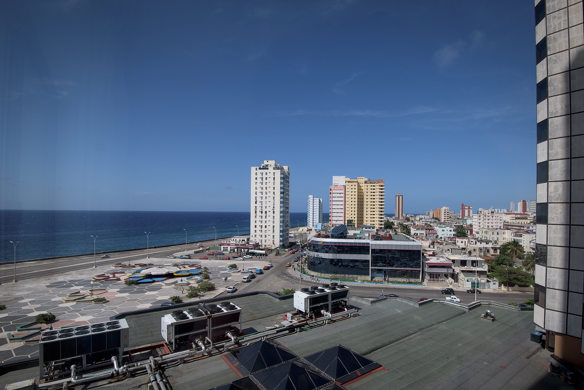 A view to the Malecon, with its major ring road around the city, with no traffic and virtually empty parking lots at 5 PM on a weekday.