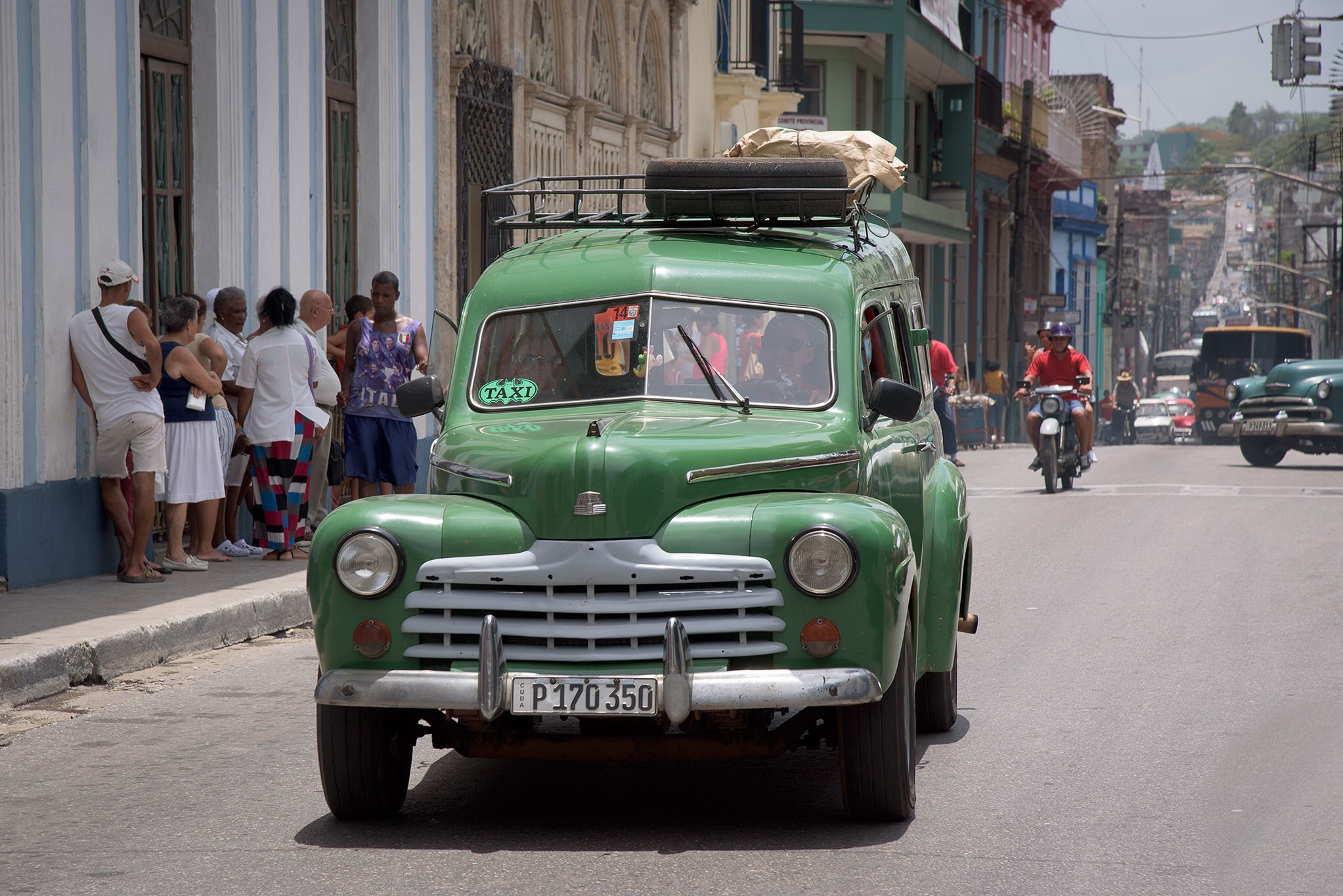 Cars, trucks, motorcycles, buses, on the road in Matanzas, most Cubans (seen waiting here) take the bus!