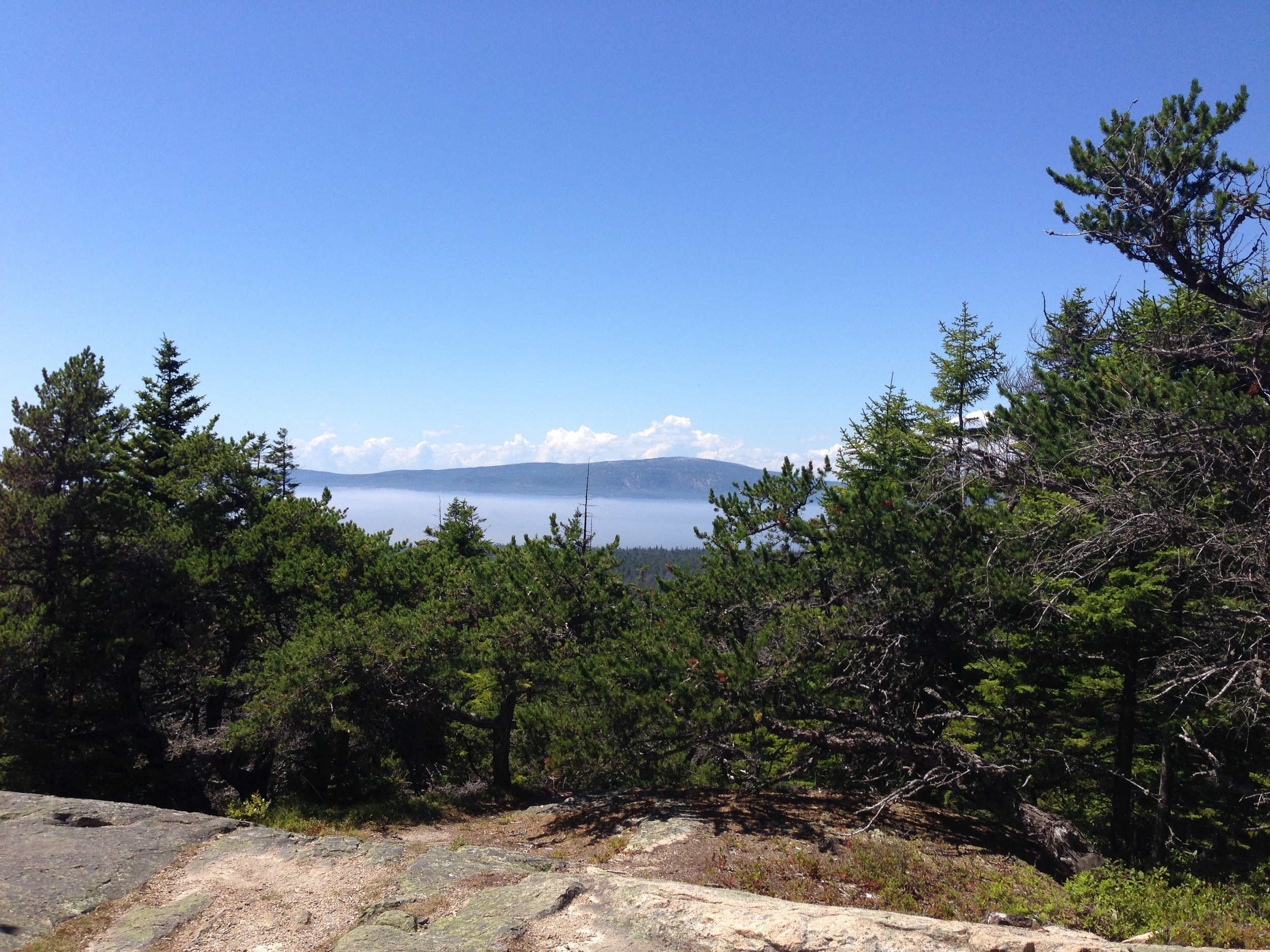"""Overlook across Mount Desert Narrows of Frenchmans Bay and MDI from the parking area at Schoodic Head; a further hike will yield even more panoramic views. On this day, another interesting Maine weather feature is visible, a thin """"marine"""" layer of fog clouds sometimes formed on top the cold water on warm days."""
