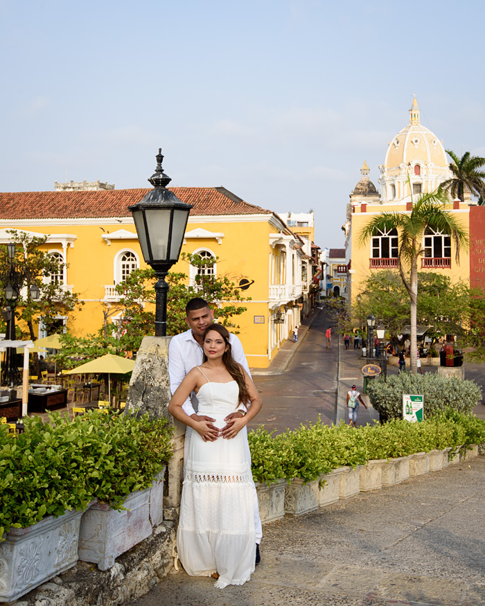 A young couple poses for photos in a scenic plaza