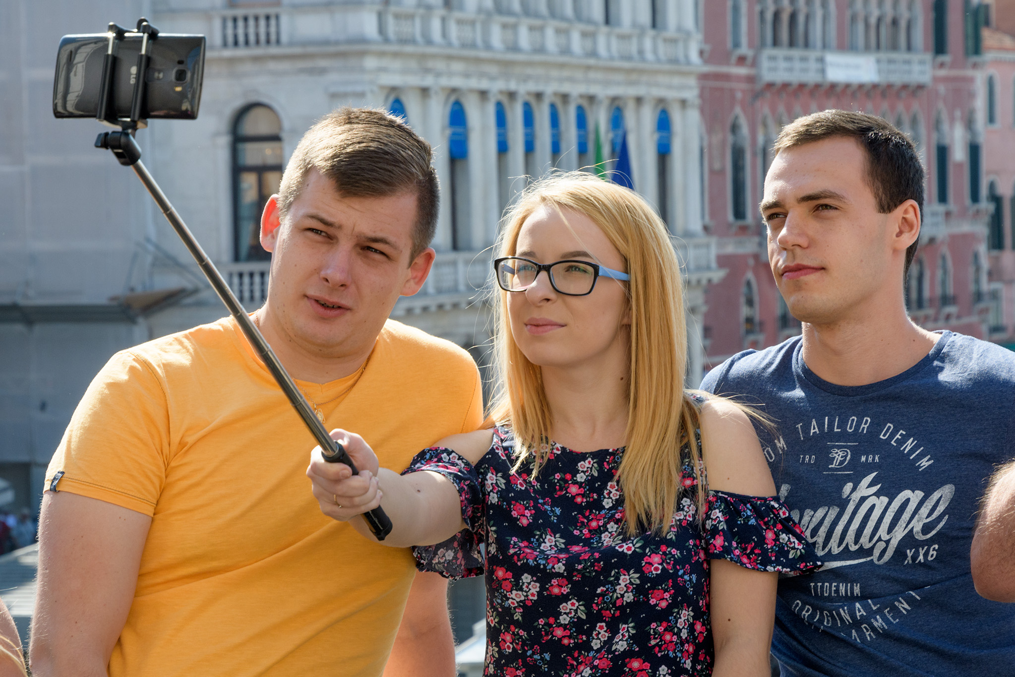 Visitors take selfies with the palazzo lined Grand Canal in the background