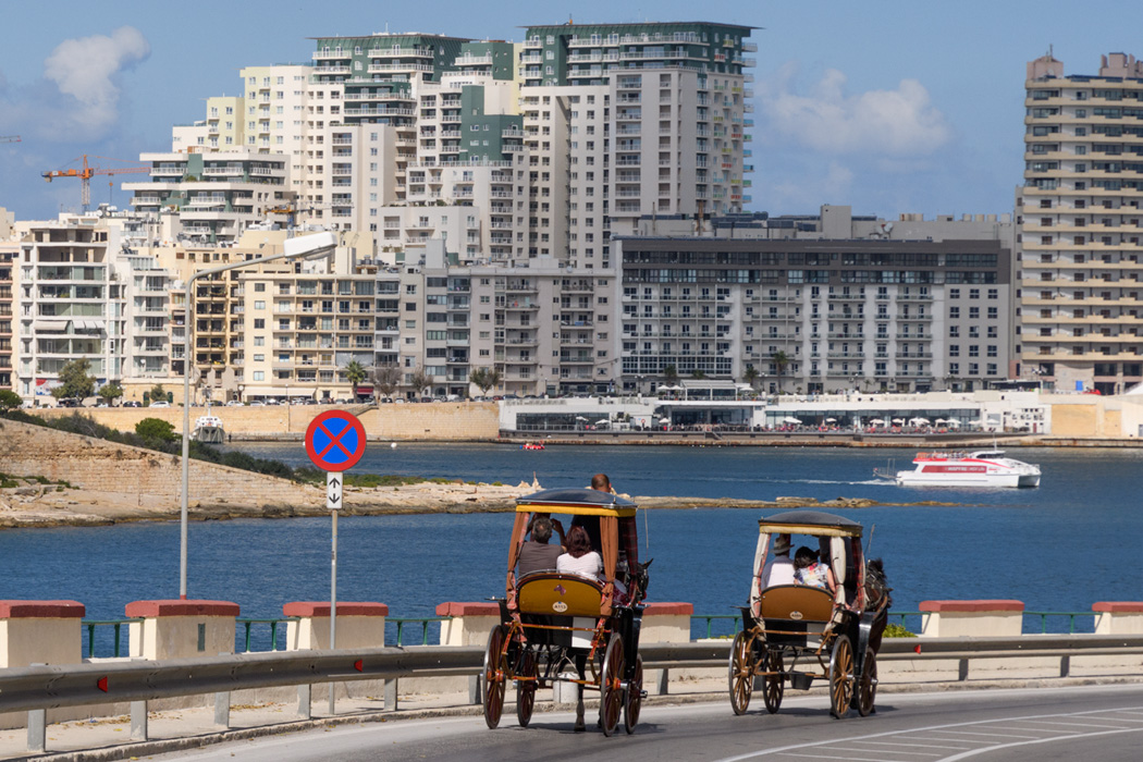 New buildings and old horse carts demonstrate the mix of old and new in Valletta.