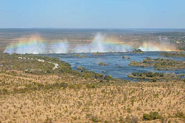 "The Victoria Falls from helicoptor, known as ""smoke that thunders"" or Mosi oa Tunya, water vapor rises from the cataracts and the sun creates rainbows.  Click on any photo below to expand."