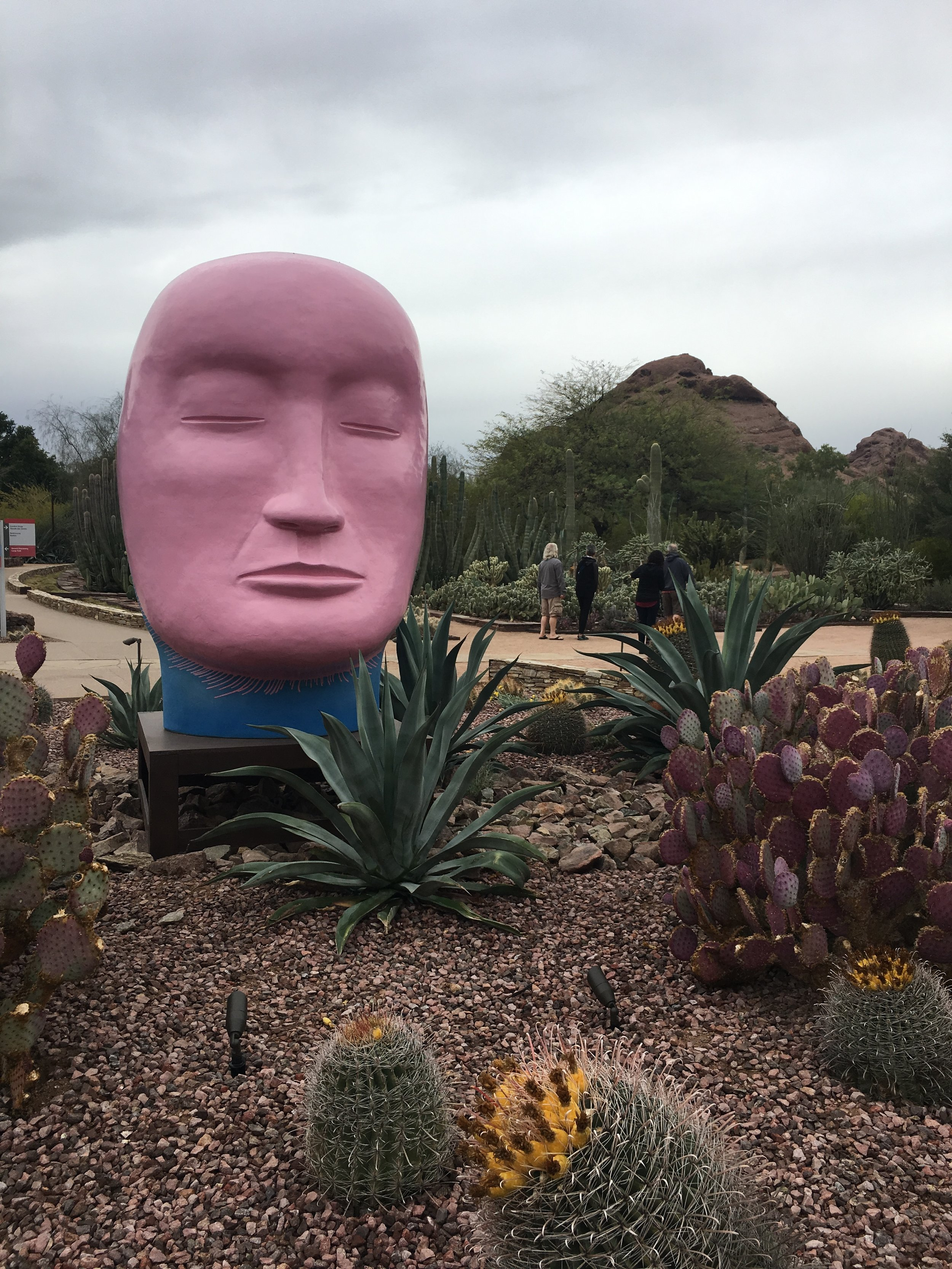 The garden features several head sculptures by Jun Keniko, as well as views of the butte