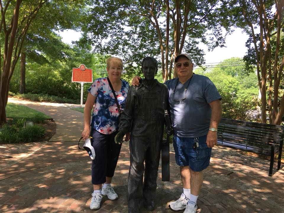 "Beverly and Bill pose with a statue of a very ""young"" Elvis which commemorates his childhood in Memphis TN"