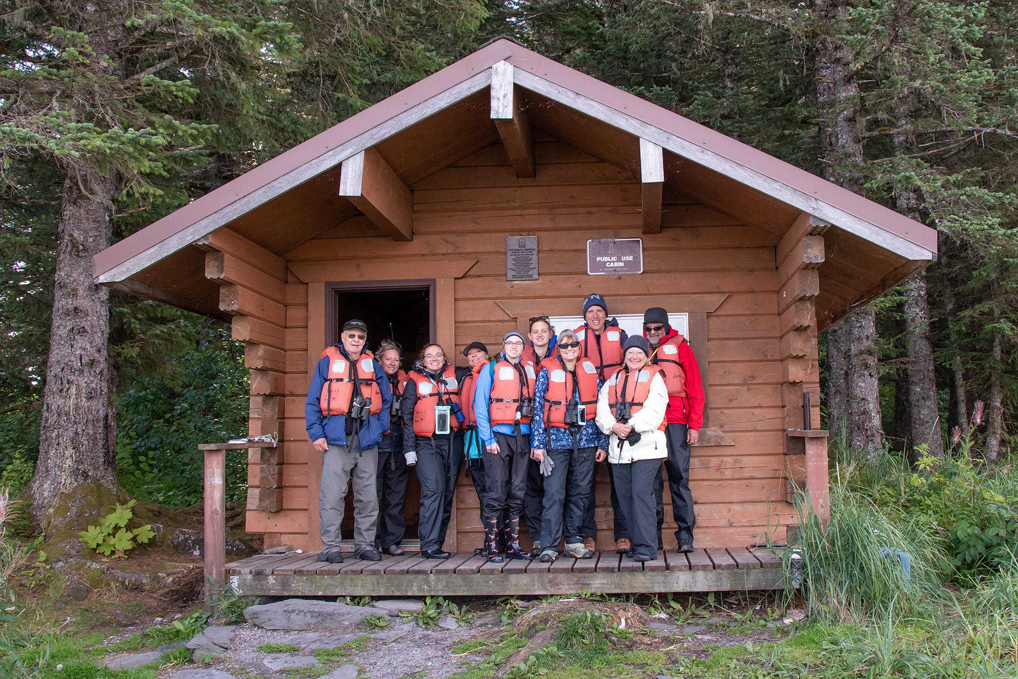 A group of all ages, enjoys a skiff tour to Hines cabin,  managed by the parks service.