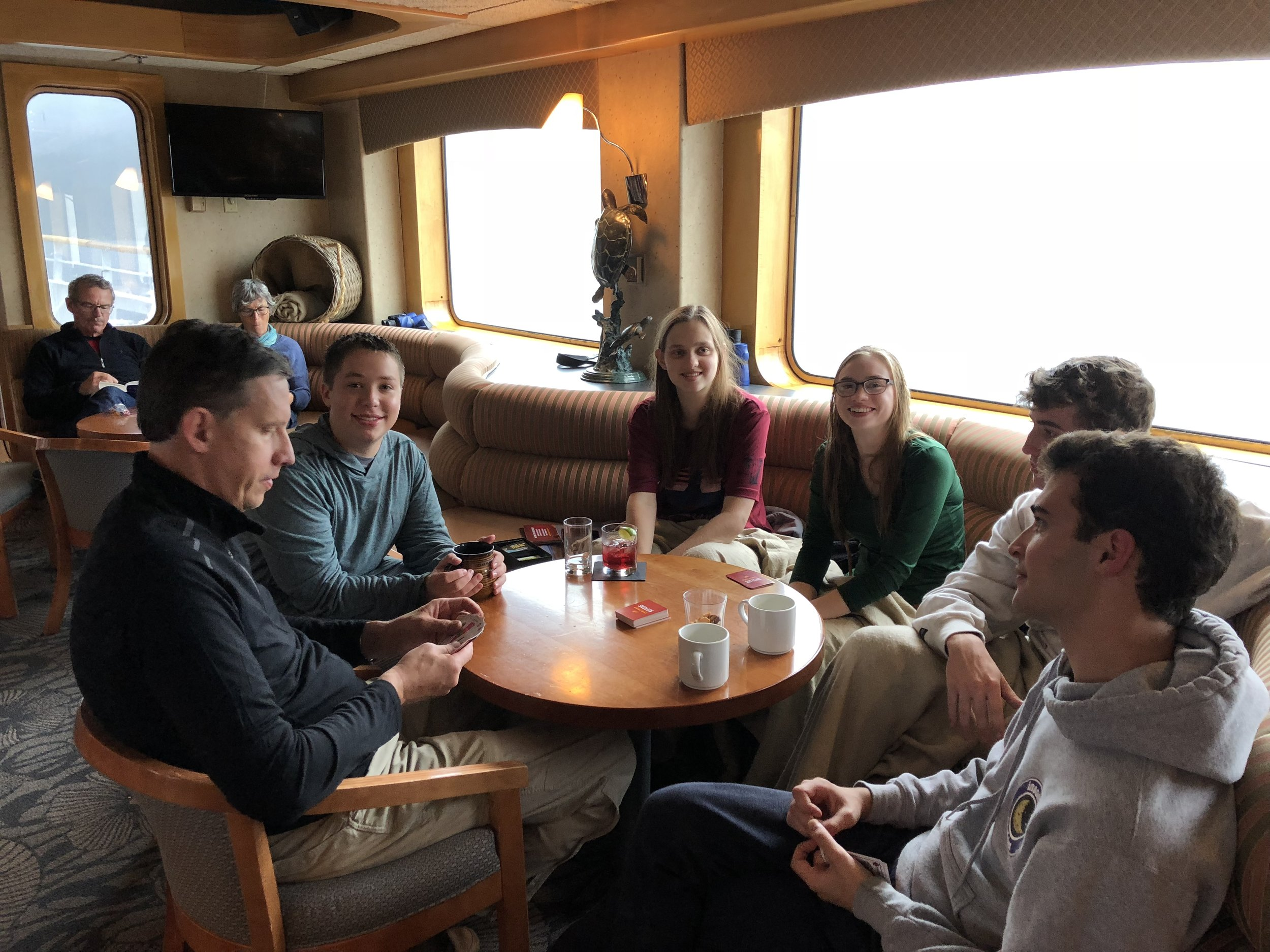 A group on board enjoys a card game in the lounge