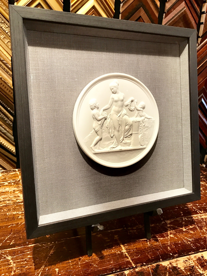 Small relief sculpture floated on gray linen and shadowboxed in charcoal.