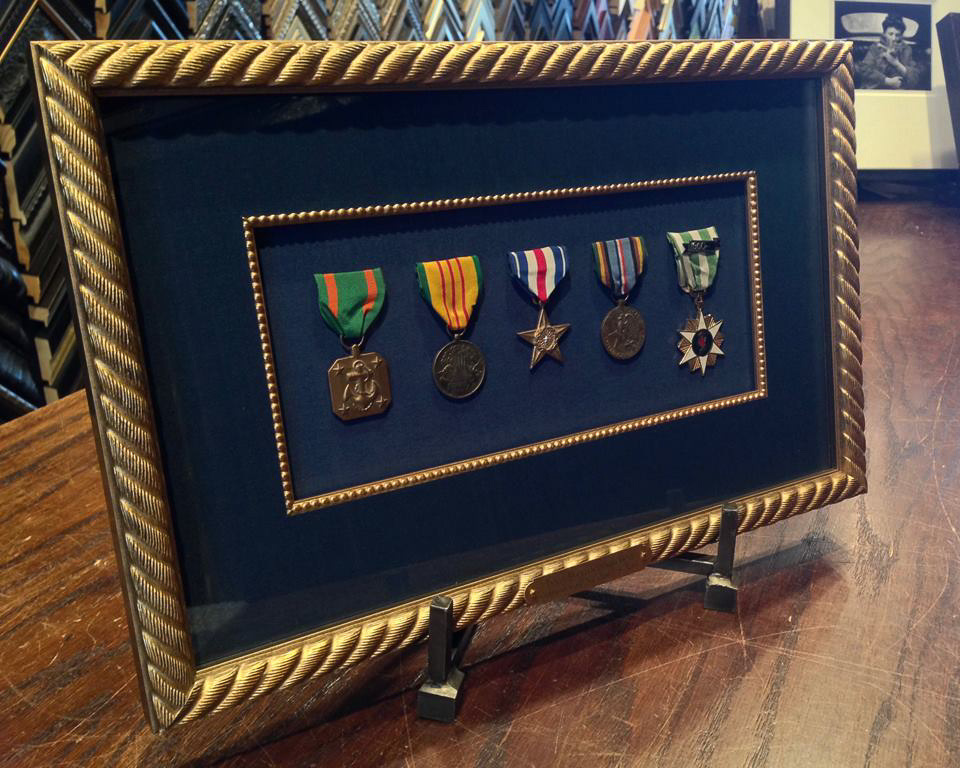 Medals mounted on blue fabric, framed in gold.