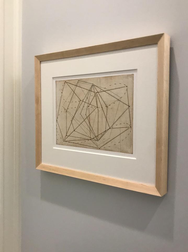 Beautiful geometric print framed in angled maple.