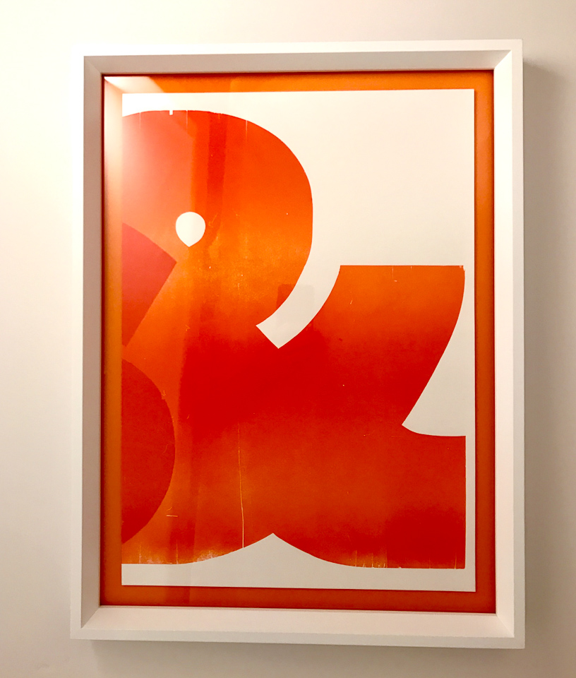 Graphic ampersand floated on orange and framed in white.