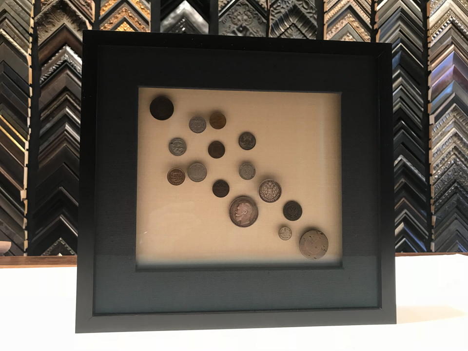 Grandfather's coins. Floated on layers of glass to lift and separate the collection. Framed in charcoal on maple with fabric matting and background