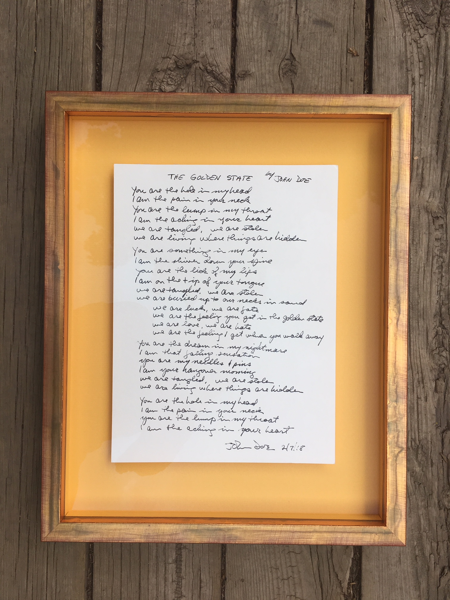 Handwritten lyrics by X.  Floated on and framed in gold to coordinate with song.