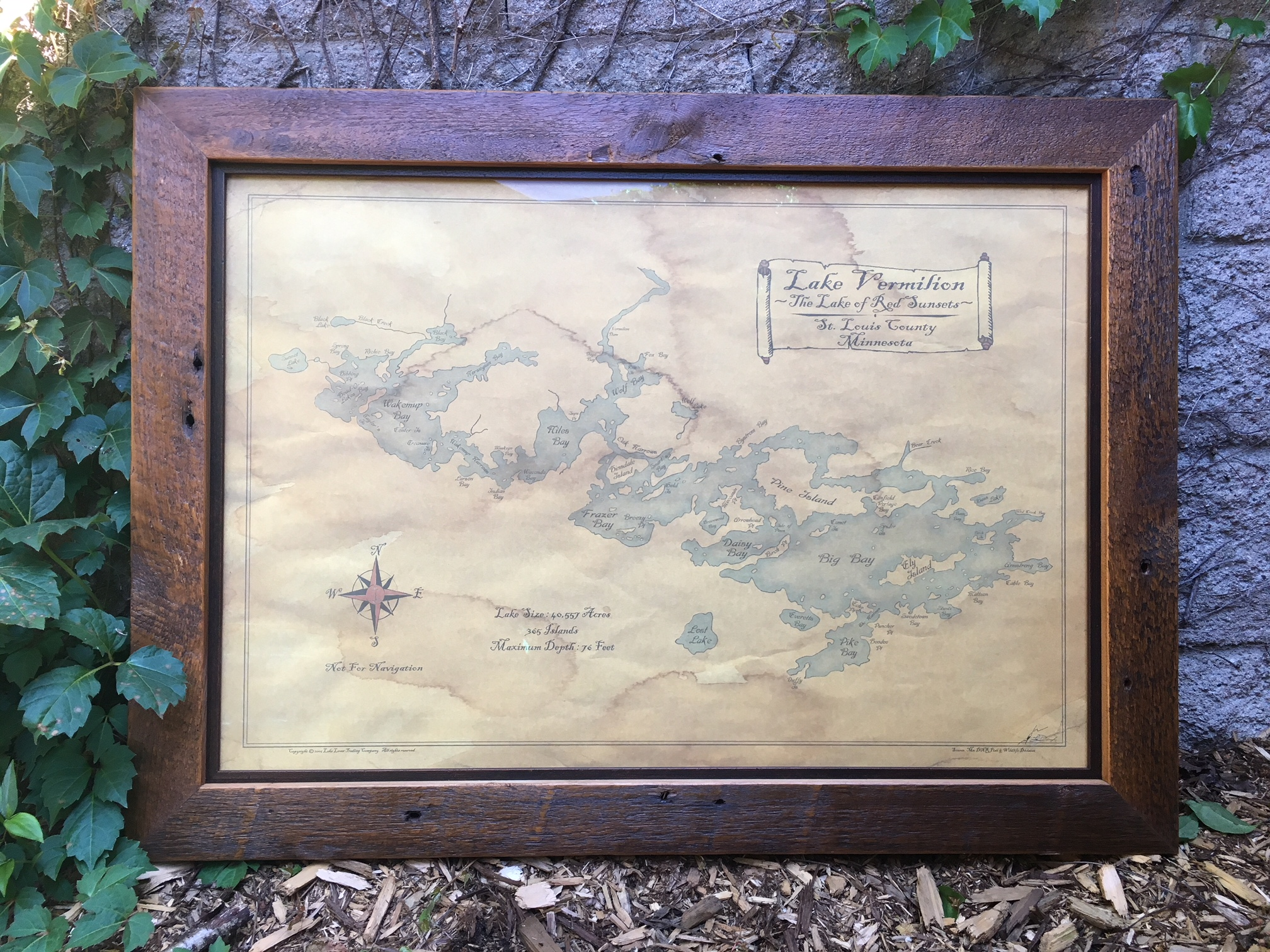 Reproduction of a vintage lake map framed in reclaimed wood with dark walnut insert.