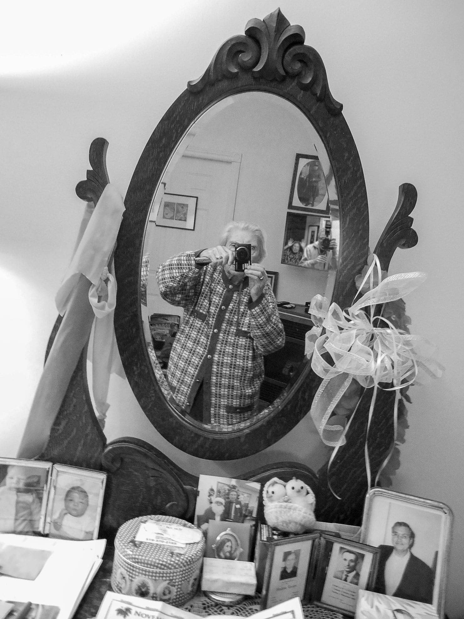 Elia Luciani's self-portrait from a mirror on a dresser covered with family photographs. (Elia Luciani)