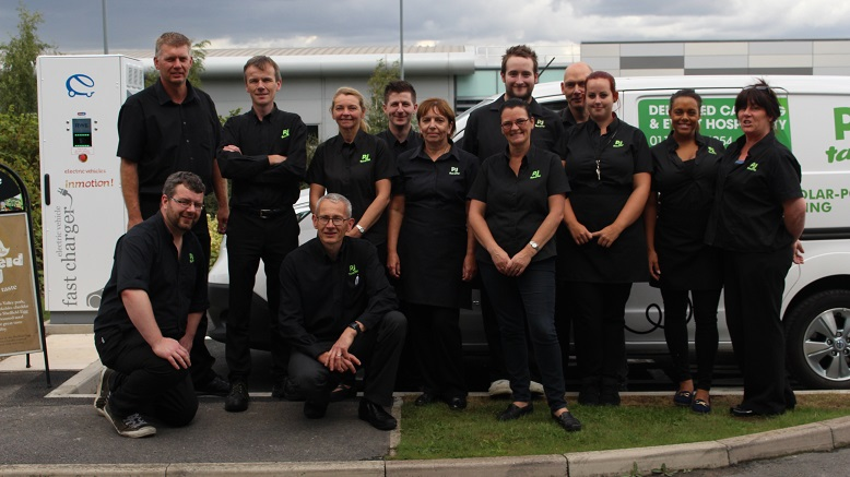 The PJ taste team posing with one of the business's electric delivery vehicles