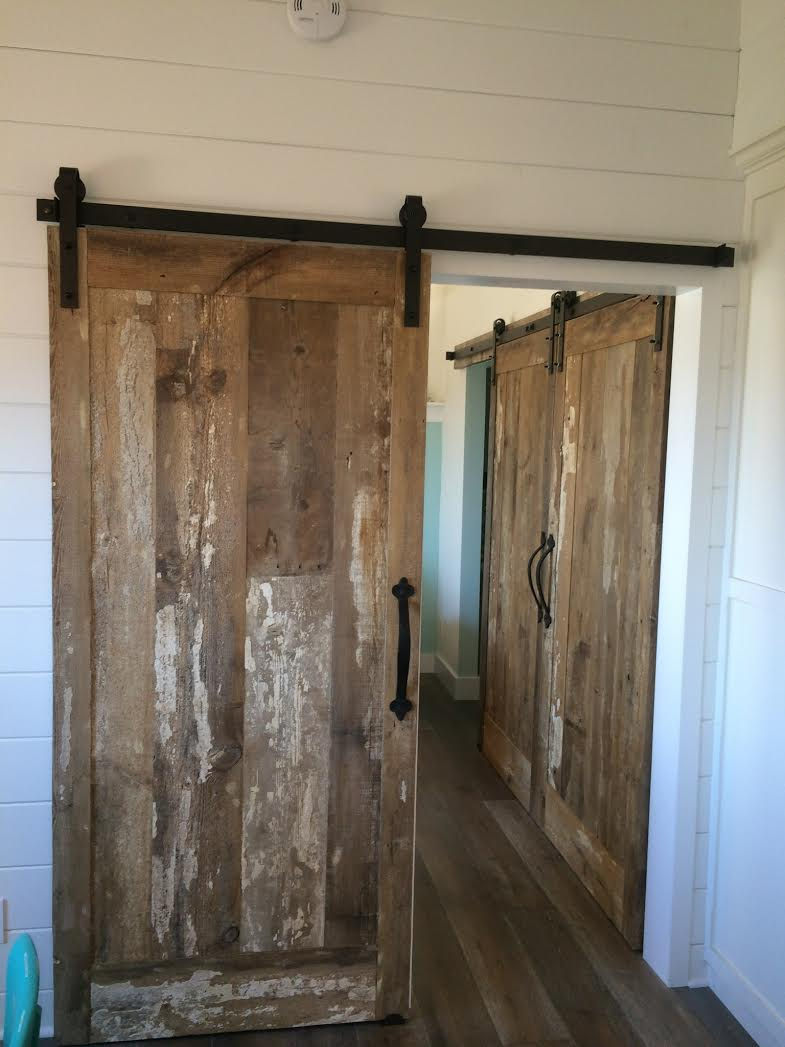 These custom designed reclaimed wood rolling track barn doors were handcrafted to fit the specs of this room divide. The rolling track hinges provide an easy access closure from one room to the other. They allow for privacy as well as create an accent piece for  both rooms. These doors turned out great & help customize this clients home.