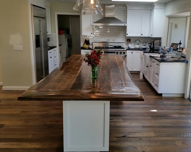 This kitchen island counter top was custom designed with our client incorporating boards she picked as well as ones we added to create the multi-tones & live edge texture look she wanted for her new kitchen remodel .It turned out beautifullyand it accents her reclaimed wood flooring also from U.S. Reclaimed.