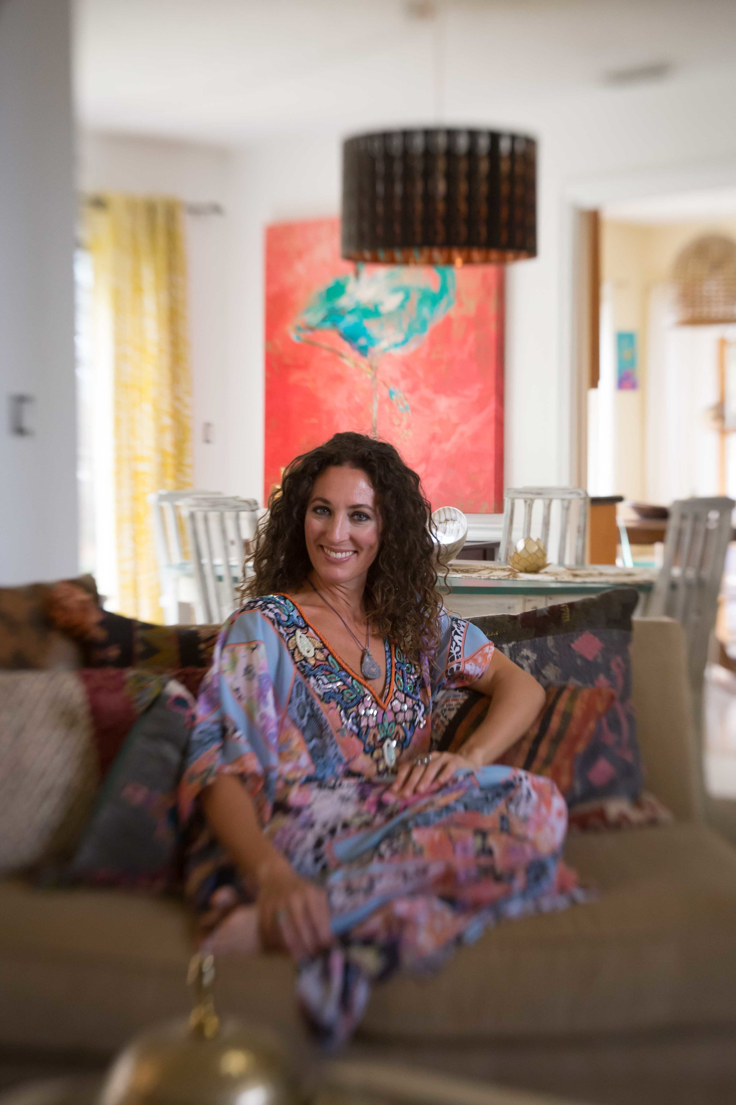 woman sitting on a couch in her beautifully decorated home
