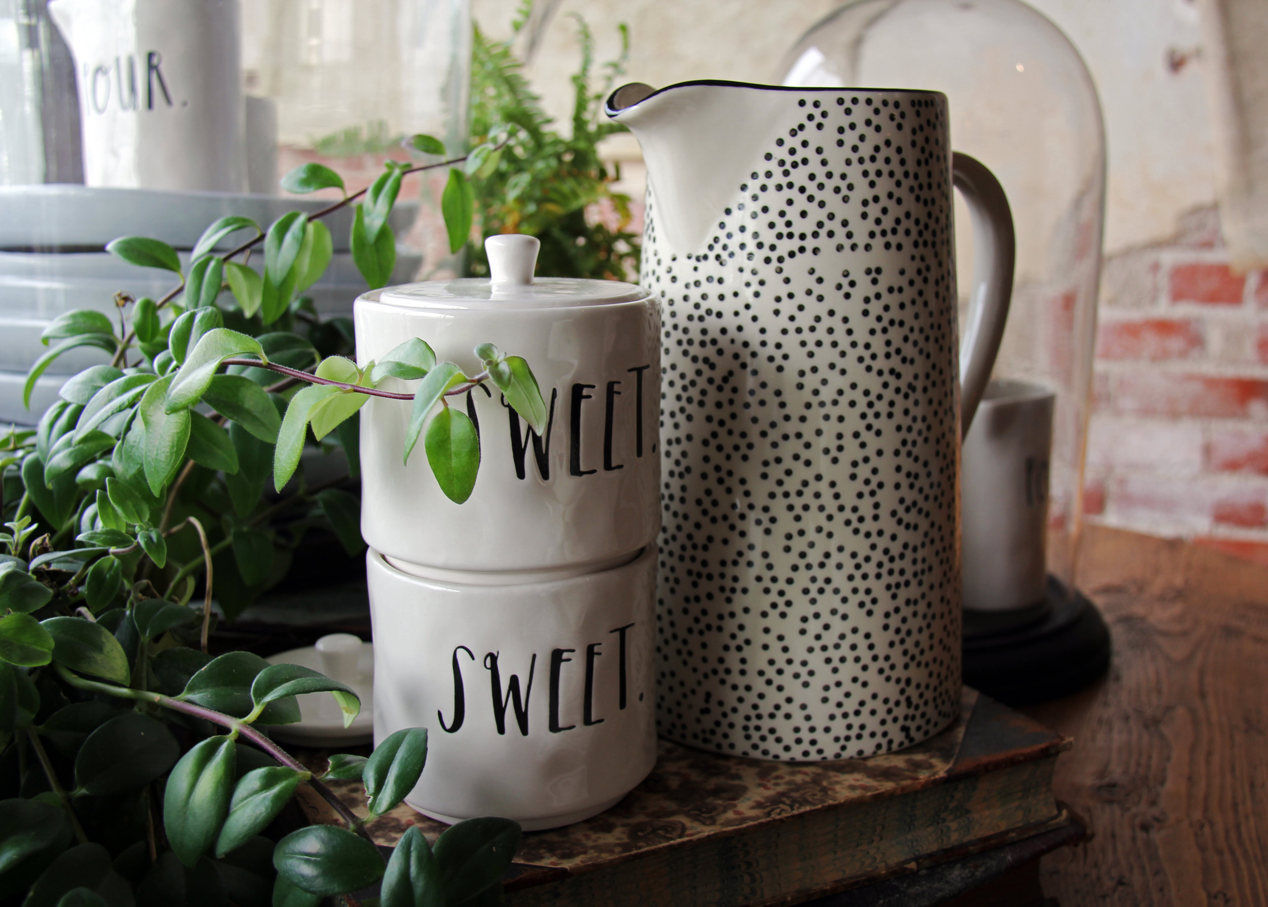"Sugar bowls appropriately adorned with ""Sweet"" lettering and cheerfully patterned pitchers"