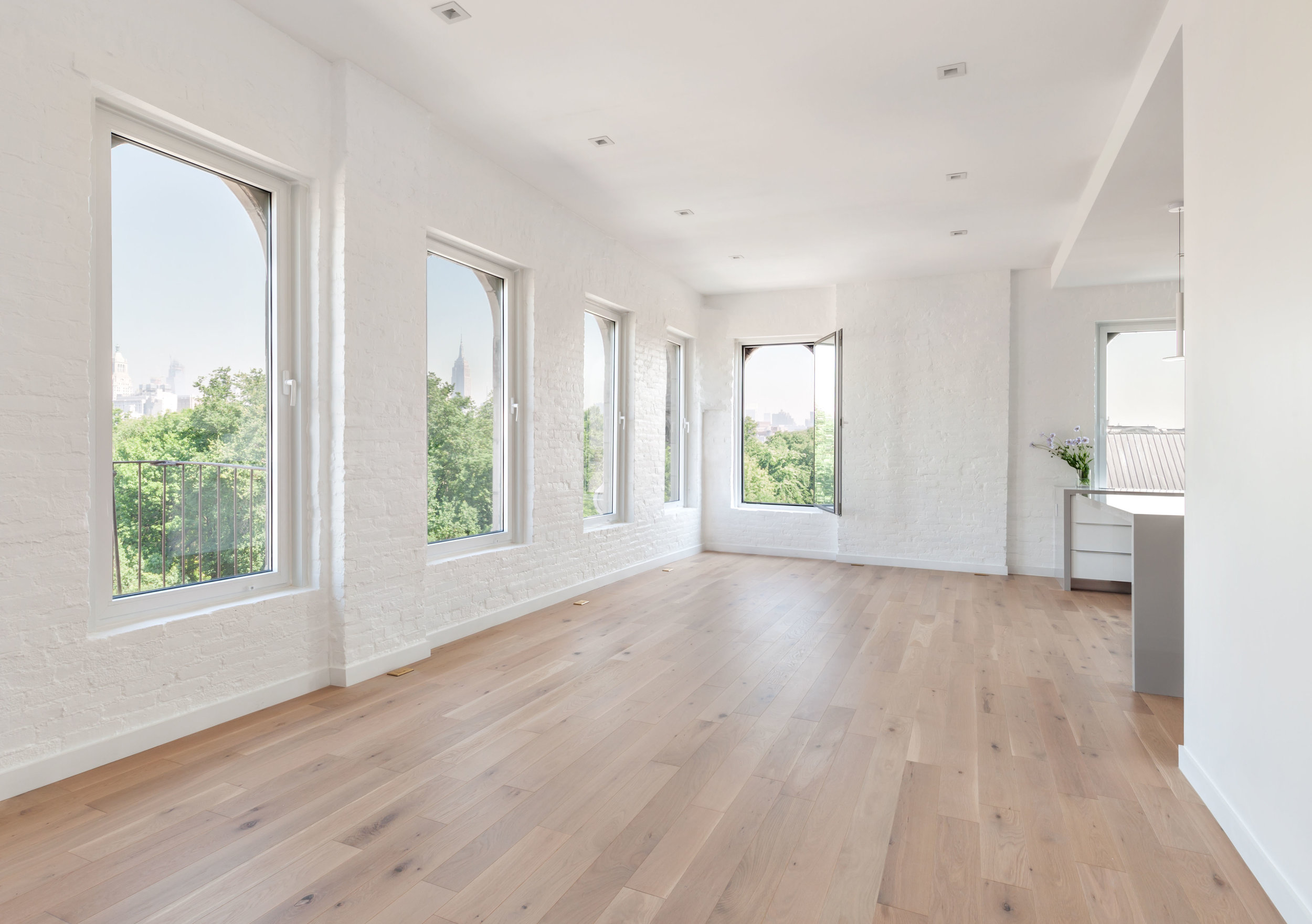 Warm, oak floors and white painted brick walls brighten space, providing a timeless, neutral canvas for years to come. New windows enhance the sweeping  skyline views.