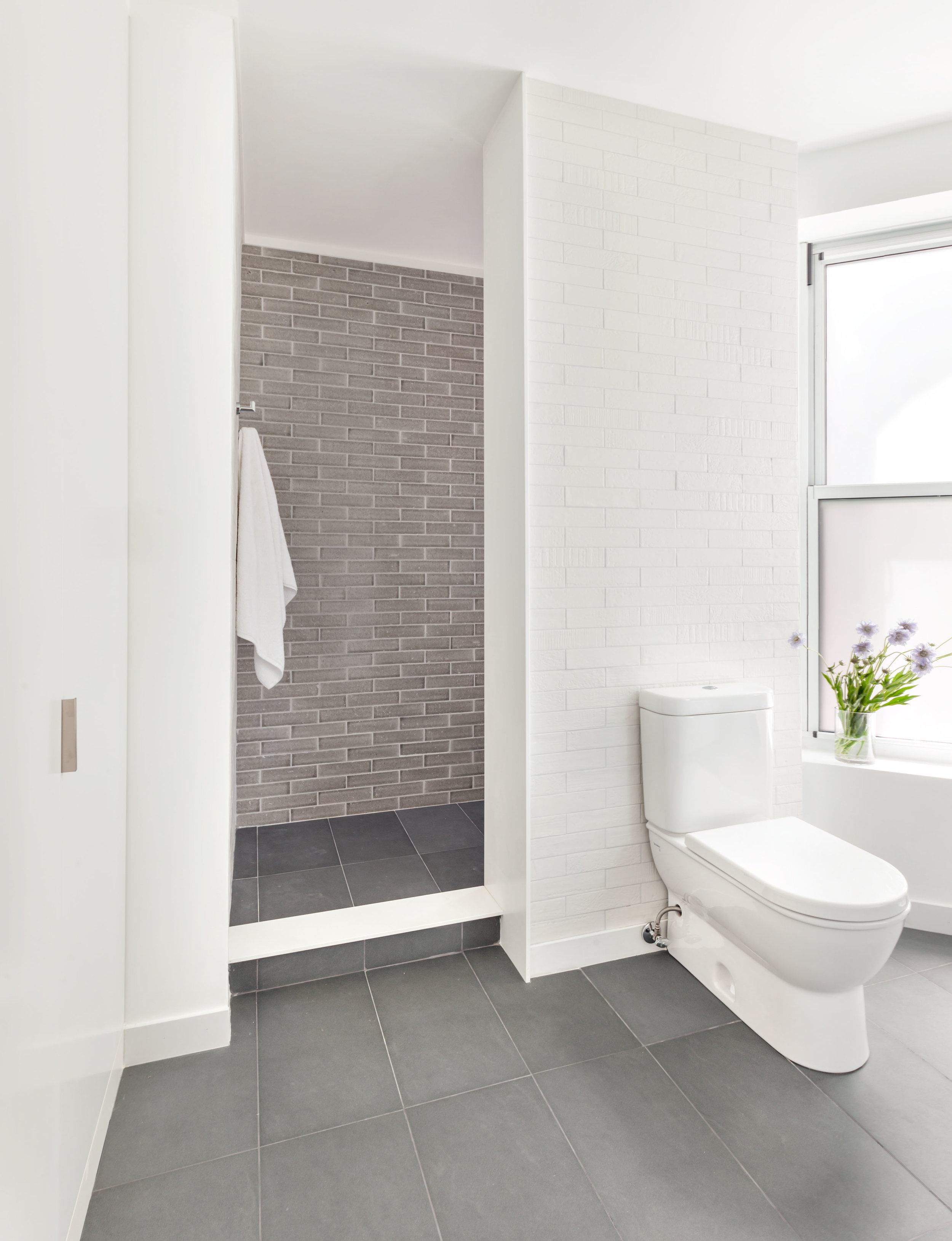 Ensuite master bathroom with white, brick textured tile and gray accent tile in the shower.
