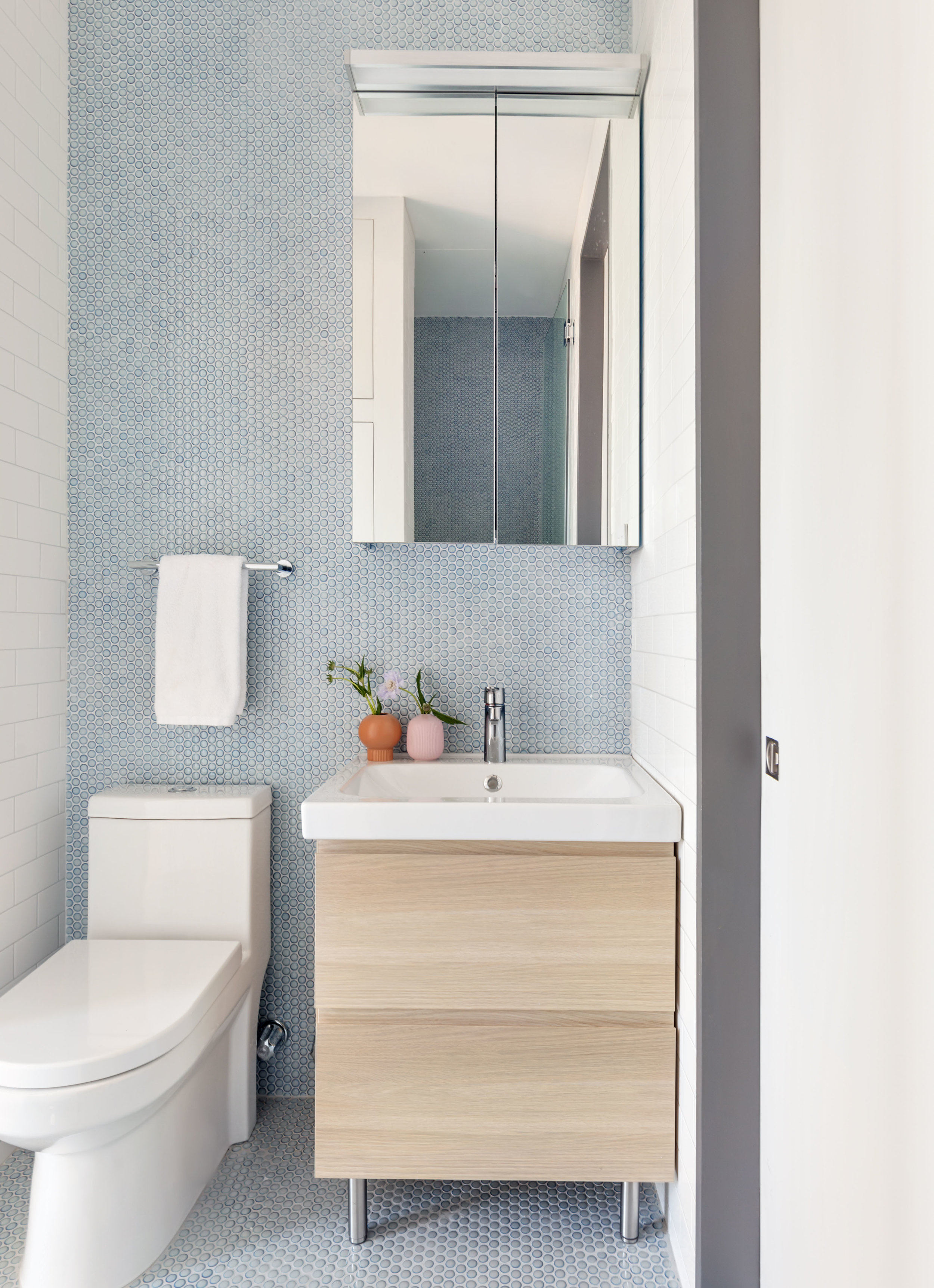 Guest bathroom with blue penny tile walls and floor.