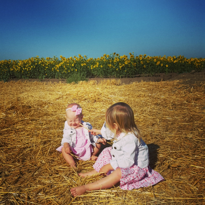 When you dress your kids in darling matching outfits and put them in a sunflower field to capture a magical moment and your toddler uses this opportunity to poke her sister in the eye with hay.
