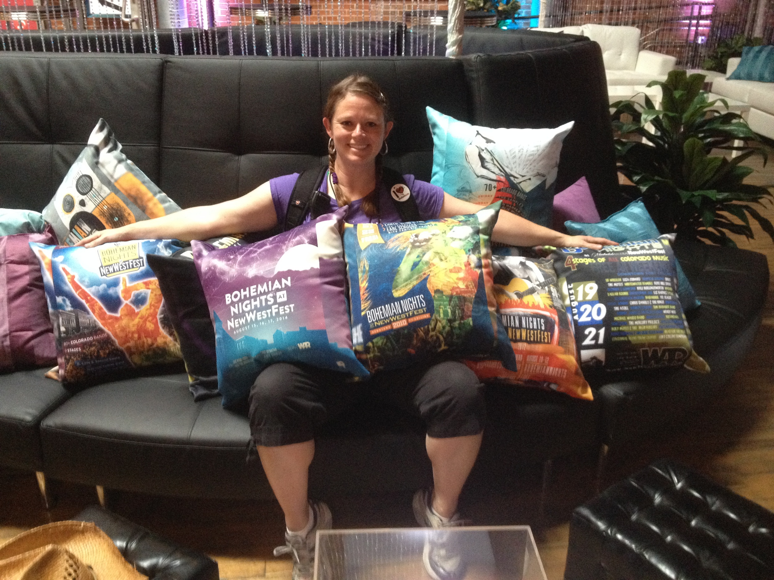 Peggy, festival director, with the collection of over 10 years of Bohemian Nightsat NewWestFest branding (pillows!)