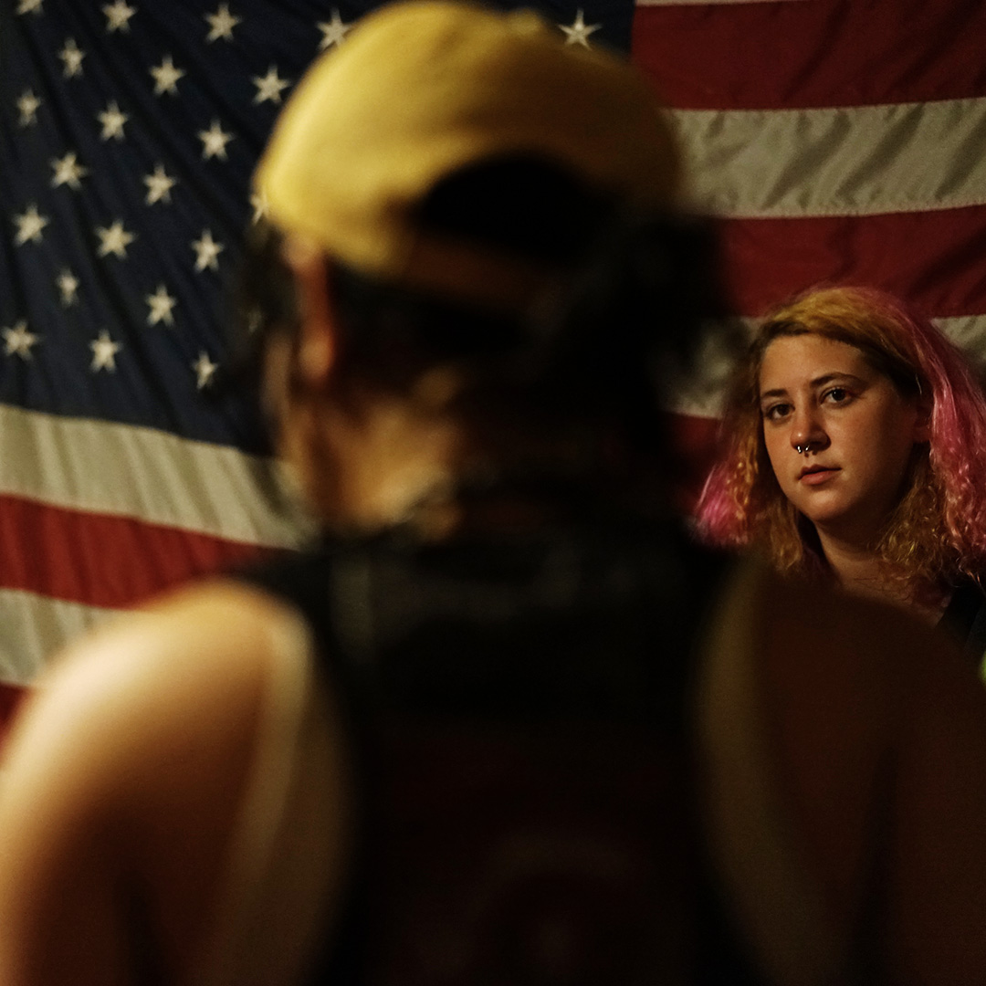 An alternative youth rests against the Stars and Stripes at a house-held punk concert mostly attended by homeless teenagers and young adults. Little Rock, AR.