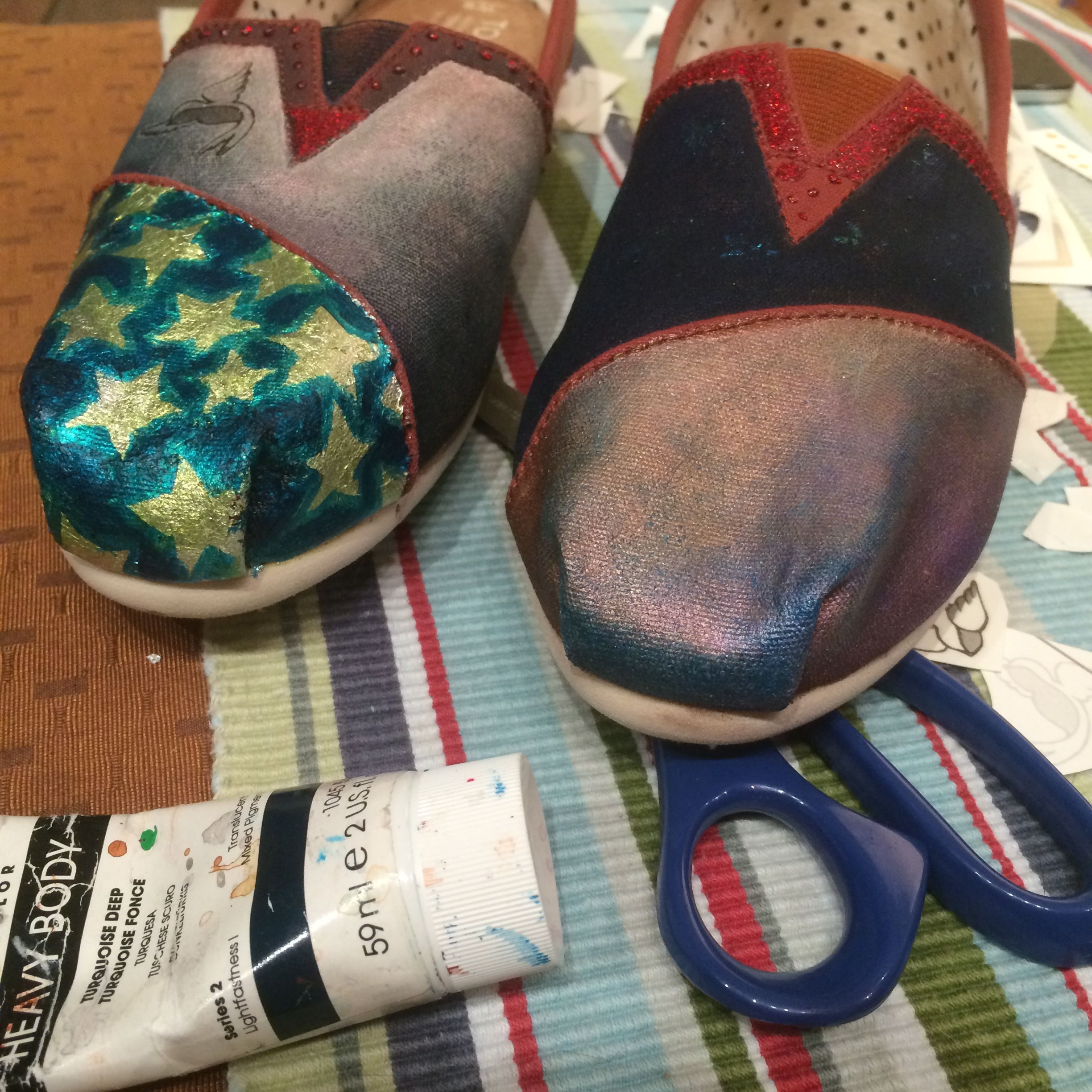 The eyeshadow is sealed with a gel medium and some glazes of paint are added. I also add a temporary tattoo of a bird to the other shoe and seal it.