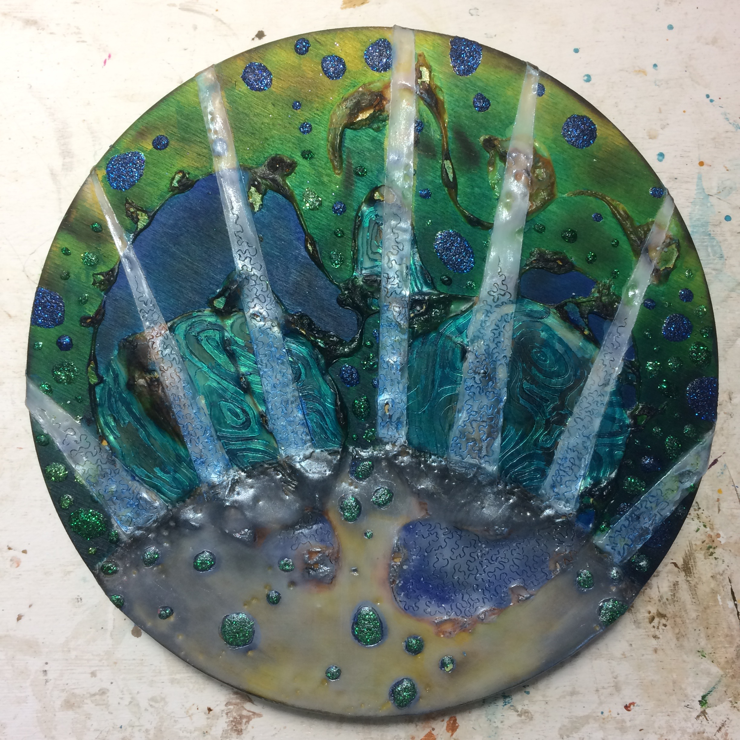 (A) Glaze of turquoise, iridescent over wax. (K) Scratched pattern into rays, blue oil stick. (A) Carved pebbles into wax.