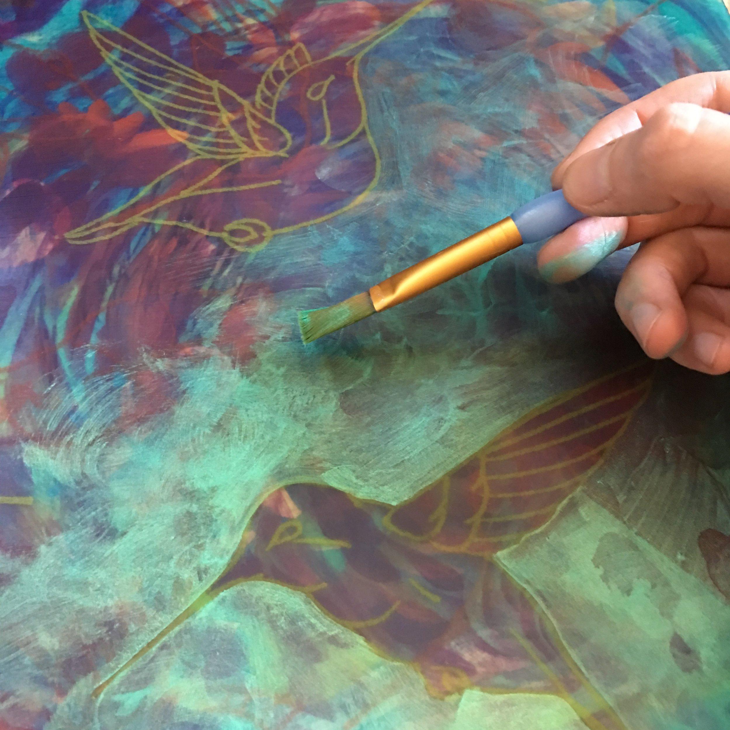 Glaze of iridescent green around transfered bird drawings.