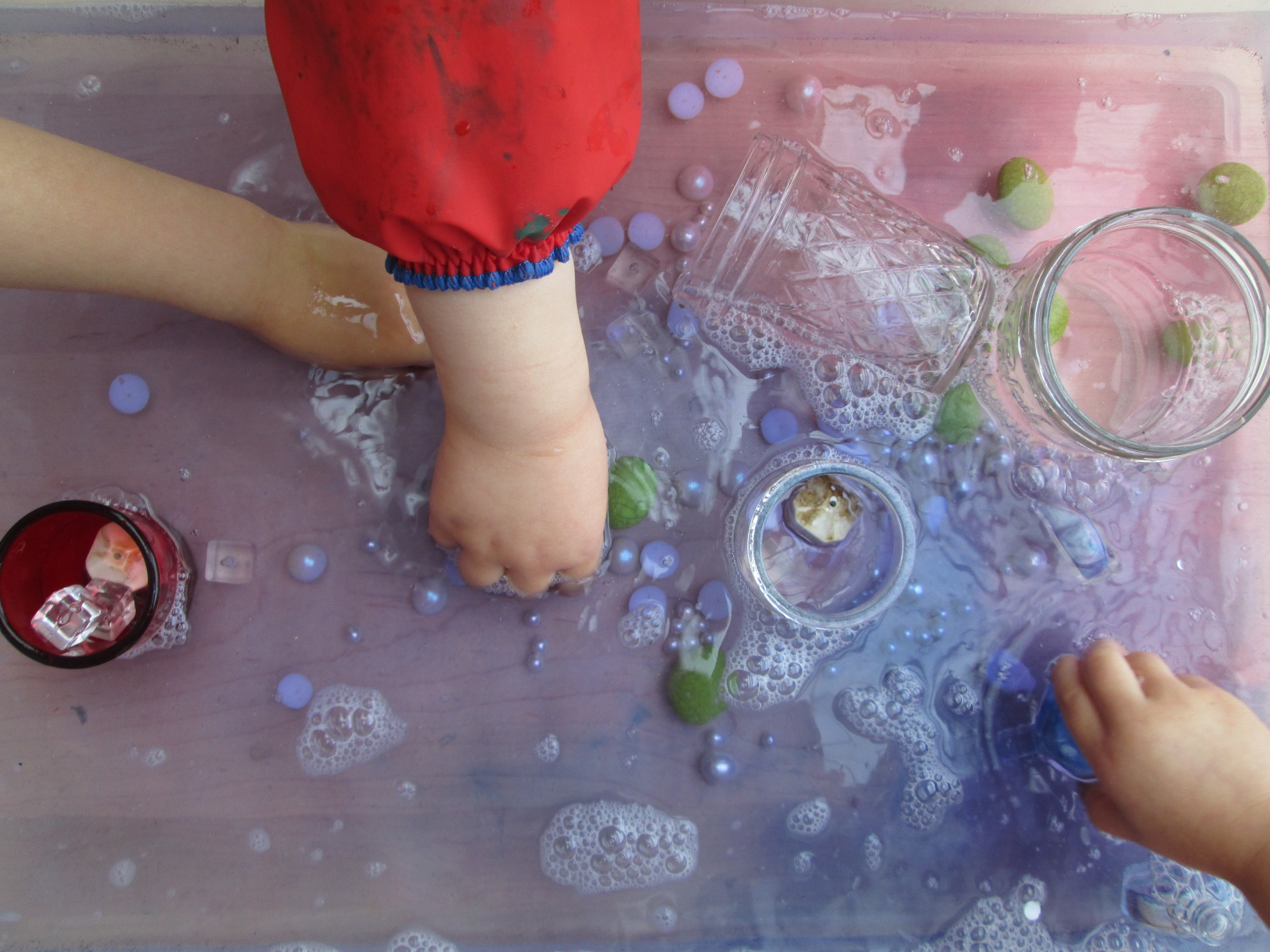 2s explore a water table full of found materials and a variety of liquid watercolor shades.