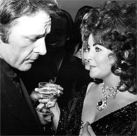 Elizabeth Taylor with Richard Burton looking impossibly glamorous, wearing her sapphire and diamond sautoir.