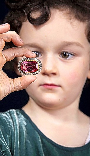 Imogen Jourdan holding the pink Imperial topaz brooch her mother bought in a junk shop for £20.  It sold for over £33,000.