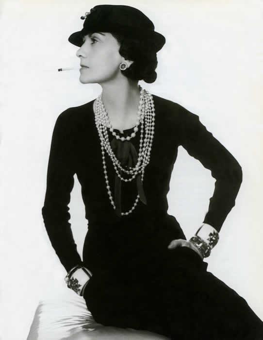 Coco Chanel wearing her trademark pearls, Verdura cuffs and signature cigarette.