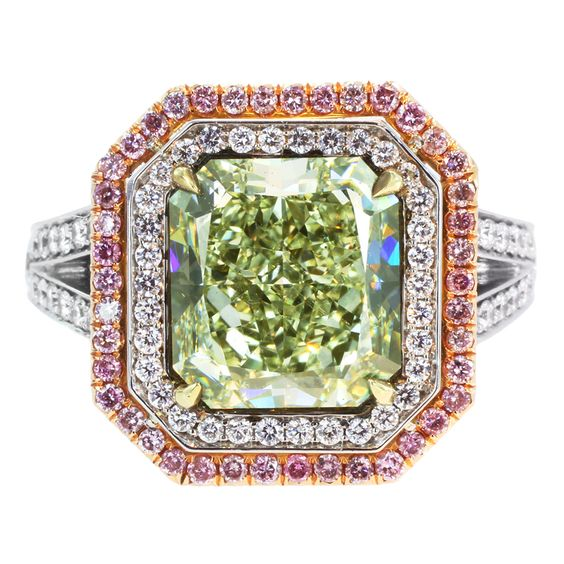 A yellowish green diamond surrounded by pink and white diamonds. A perfect example of how much the greens can vary from stone to stone.