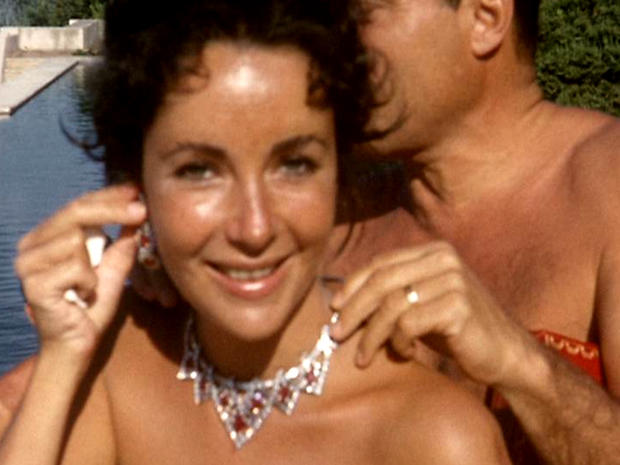 A still from a home movie showing Mike Todd fastening the necklace he has just given Elizabeth Taylor.