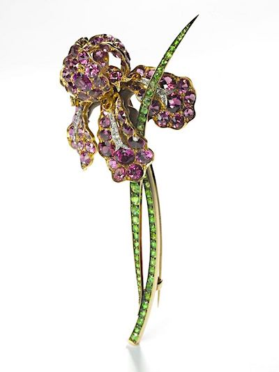 A highly naturalistic iris brooch in purple sapphires, demantoid garnets and diamonds by Louis Comfort Tiffany.